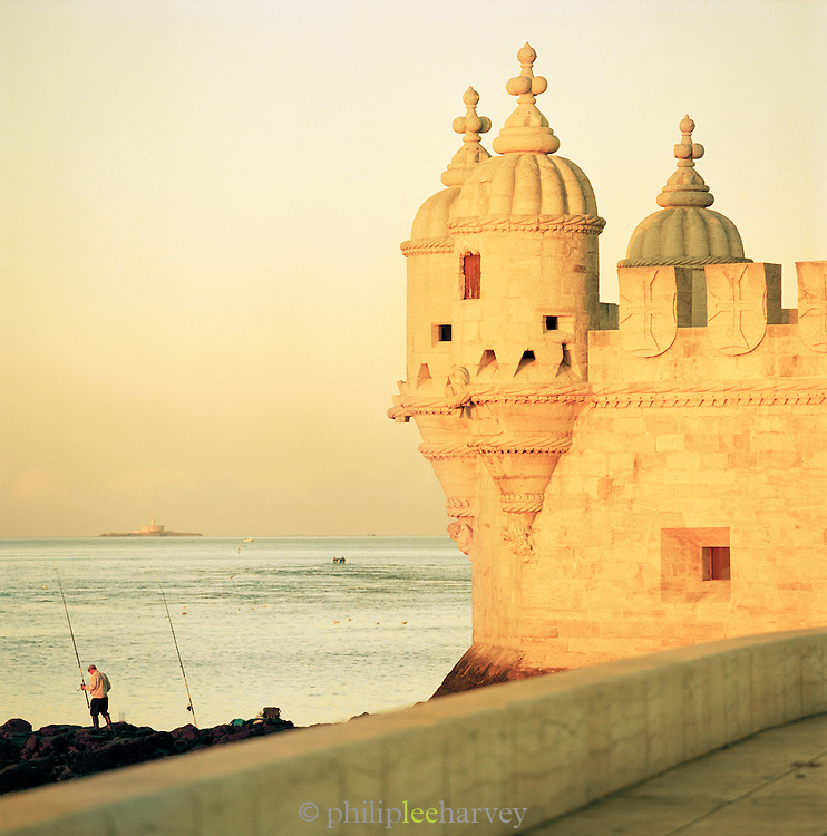 A man fishes next to the Belém Tower, built in the early 16th century, in Lisbon, Portugal