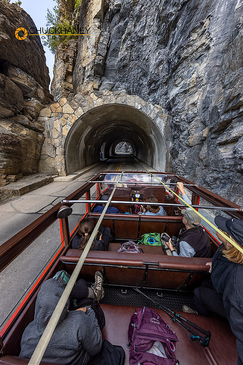 Iconic Red Jammer bus entering westside tunnel in Glacier National Park, Montana, USA