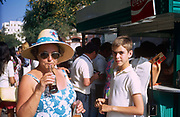 A mother and adolescent boy sip soft drinks while on a daytrip to Malaga on the Costa del Sol, southern Spain. Wearing a floppy hat and a matching floral blue dress, the mother takes sips from her Coke bottle at an outside street kiosk outside the bullfighting ring in the centre of town. The 70s saw an explosion of UK tourism to the Spanish costas, providing middle and working class with affordable holidays, a few hours flying time from Britain.