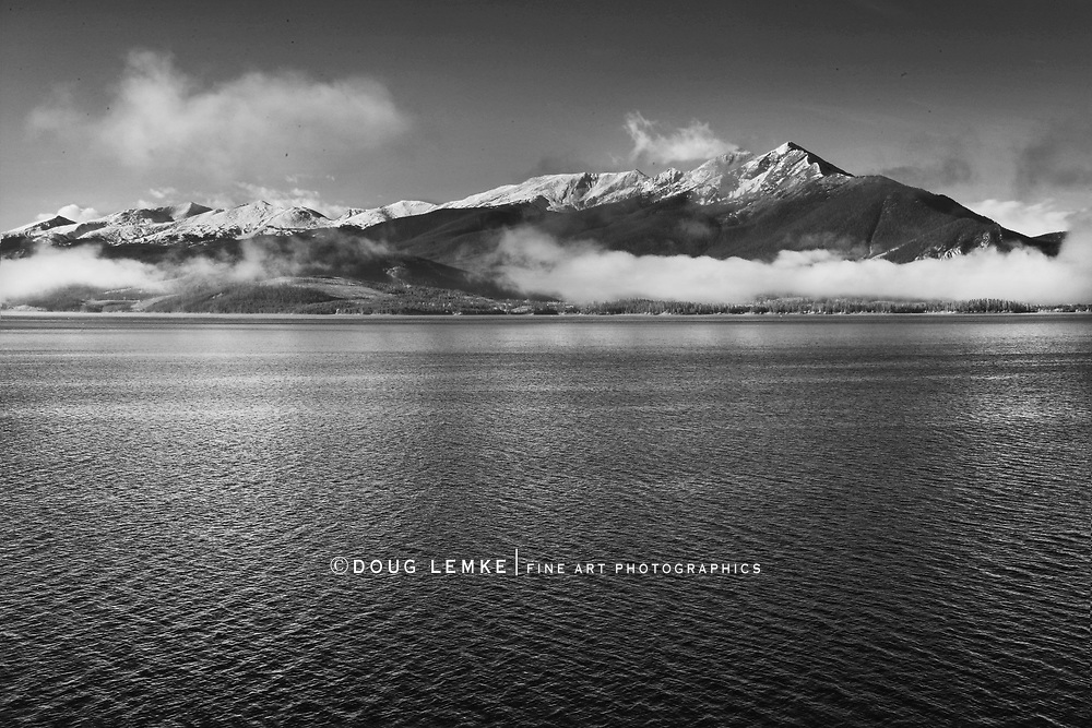 Snow capped peaks stand above an early morning cloud that sits on the surface of the Dillon Reservoir at Dillon Colorado during autumn, black and white version, Colorado Rockies, USA