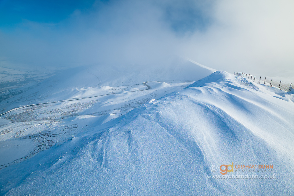 Snow patterns on Rushup Edge looking towards Mam Tor, which is enshrouded in low cloud. A misty winter landscape in the Derbyshire Peak District. England, UK.