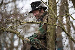 Steeple Claydon, UK. 24 February, 2021. An activist observes from a tree the eviction by Thames Valley Police officers acting on behalf of HS2 Ltd of fellow activists opposed to the HS2 high-speed rail link from ancient woodland known as Poors Piece. The activists created the Poors Piece Conservation Project there in spring 2020 after having been invited to stay on the land by its owner, farmer Clive Higgins.