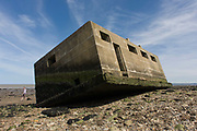 WW2-era concrete pillbox defence structure lies on the beach after coastal erosion at Warden Point, Isle of Sheppey, Kent. As part of Britain's coastal defences in the 1940s, beaches were mined and concrete bunkers  installed as lookouts facing out so sea and in the event of an invasion by German forces, as firing positions. Overhead, the Luftwaffe flew on their way to London during the Blitzkrieg. More recently, they have fallen into the sea after coastal erosion continues to wash the sedimentary soil (from the Eocene geological epoch of 52-51 million years ago) into the tidal waters of the Thames estuary. Chain Home Low Station at Warden Point was built in 1941 it stood on top of the cliffs then. Erosion of cliffs caused the remaining buildings to fall into the sea in the 1970s.