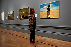 © Licensed to London News Pictures. 17/09/2013. London, UK. A member of gallery staff looks at 'Ned Kelly' (1946) (right) painted by Australian artist Sidney Nolan as part of his iconic series about the Australian outlaw, at the press view for the Royal Academy of Arts latest exhibition 'Australia' in London today (17/09/2013). The exhibition, said to be the most significant survey of Australian art ever mounted in the UK, spans more than 200 years, from 1800 to the present, and runs from the 21st of September to the 8th of December 2013. Photo credit: Matt Cetti-Roberts/LNP