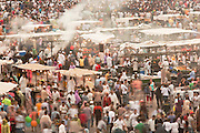 Hundreds of people walk between food stalls in the Djemaa el Fna in the medina of Marrakech, Morocco. Every night the main square fills with dozens of food vendors and their carts