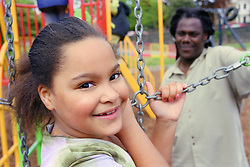 Young girl playing on climbing frame in playground with father watching,