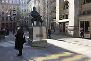 Businessmen check messages on their smartfones around the statue of philathropist, banker and entrepreneur George Peabody (1795 - 1869).