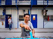 "12 FEBRUARY 2019 - SIHANOUKVILLE, CAMBODIA: A Chinese construction worker washes his dishes in the Chinese workers' labor camp in Sihanoukville. There are about 50 Chinese casinos and resort hotels either open or under construction in Sihanoukville. The casinos are changing the city, once a sleepy port on Southeast Asia's ""backpacker trail"" into a booming city. The change is coming with a cost though. Many Cambodian residents of Sihanoukville  have lost their homes to make way for the casinos and the jobs are going to Chinese workers, brought in to build casinos and work in the casinos.      PHOTO BY JACK KURTZ"