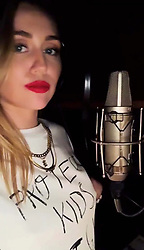 """Miley Cyrus releases a photo on Twitter with the following caption: """"""""Recording something special for the holidays!"""""""". Photo Credit: Twitter *** No USA Distribution *** For Editorial Use Only *** Not to be Published in Books or Photo Books ***  Please note: Fees charged by the agency are for the agency's services only, and do not, nor are they intended to, convey to the user any ownership of Copyright or License in the material. The agency does not claim any ownership including but not limited to Copyright or License in the attached material. By publishing this material you expressly agree to indemnify and to hold the agency and its directors, shareholders and employees harmless from any loss, claims, damages, demands, expenses (including legal fees), or any causes of action or allegation against the agency arising out of or connected in any way with publication of the material."""