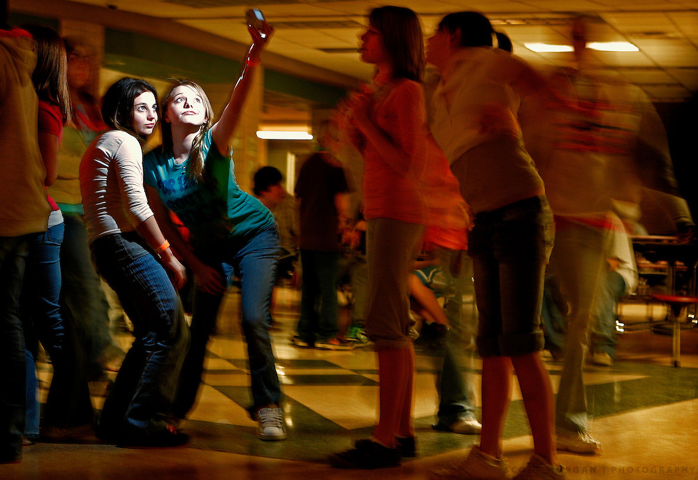 A pair of students take a picture as others dance around them in the cafeteria Friday, Jan. 25, 2008 during Rec Night at Harlem Middle School in Loves Park.<br /> SCOTT MORGAN | ROCKFORD REGISTER STAR