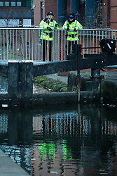 "© Licensed to London News Pictures . Manchester , UK . FILE PICTURE DATED 29/12/2013 of PCSOs looking over a canal bridge in to the River Medlock off Oxford Road in Manchester City Centre during the search for a 17 year old from Stockport , who was last seen in the early hours of Saturday 28th December in Manchester City Centre following a night out with friends . Greater Manchester Police have issued a statement after suggestions that a number of deaths in and around Manchester's canals may be linked to a serial killer , named in local folklore as "" The Pusher "" . The statement said "" Absolutely no evidence whatsoever of foul play has been established "" . Photo credit : Joel Goodman/LNP"