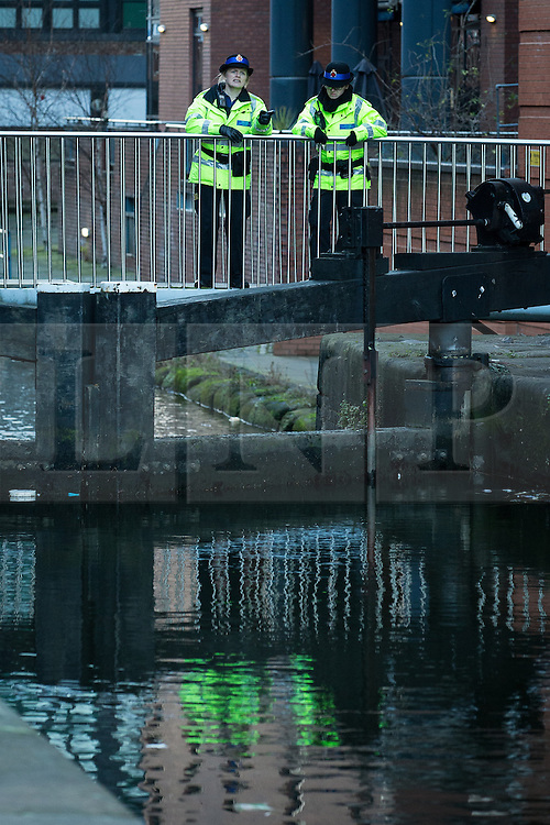 """© Licensed to London News Pictures . Manchester , UK . FILE PICTURE DATED 29/12/2013 of PCSOs looking over a canal bridge in to the River Medlock off Oxford Road in Manchester City Centre during the search for a 17 year old from Stockport , who was last seen in the early hours of Saturday 28th December in Manchester City Centre following a night out with friends . Greater Manchester Police have issued a statement after suggestions that a number of deaths in and around Manchester's canals may be linked to a serial killer , named in local folklore as """" The Pusher """" . The statement said """" Absolutely no evidence whatsoever of foul play has been established """" . Photo credit : Joel Goodman/LNP"""