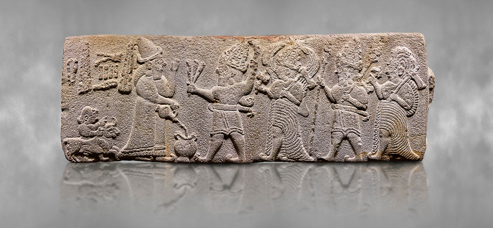 Aslantepe Hittite relief sculpted orthostat stone panel. Limestone, Aslantepe, Malatya, 1200-700 B.C. . Anatolian Civilisations Museum, Ankara, Turkey<br /> <br /> Scene of the king's offering drink and sacrifice to the gods. King pours from the pitcher to the vessel (libation); behind the king is a servant bringing a sacrifice. Storm God across the king holds Teshup, a triple lightning bundle - sickle, and a spear-mace set in the other orthostat; the goddess Ishtar holds weapon in both. All six figures have shoes with the curled ends. <br /> <br /> Against a grey art background. <br /> <br /> If you prefer to buy from our ALAMY STOCK LIBRARY page at https://www.alamy.com/portfolio/paul-williams-funkystock/hittite-art-antiquities.html . Type - Aslantepe - in LOWER SEARCH WITHIN GALLERY box. Refine search by adding background colour, place, museum etc.<br /> <br /> Visit our HITTITE PHOTO COLLECTIONS for more photos to download or buy as wall art prints https://funkystock.photoshelter.com/gallery-collection/The-Hittites-Art-Artefacts-Antiquities-Historic-Sites-Pictures-Images-of/C0000NUBSMhSc3Oo