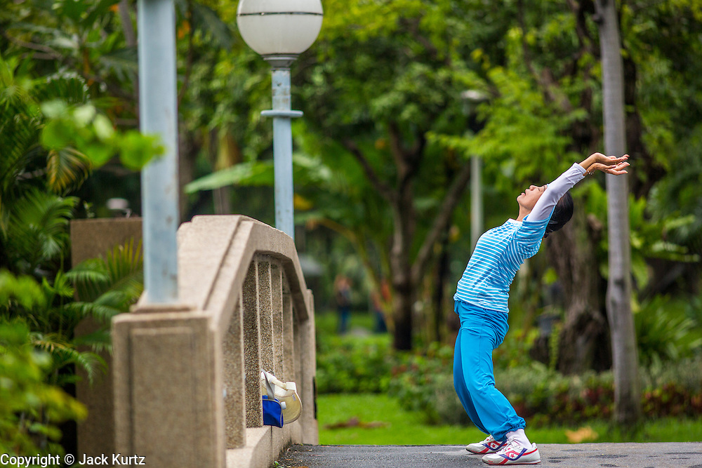 06 OCTOBER 2012 - BANGKOK, THAILAND:  A woman stretches while exercising in Lumphini Park in Bangkok. The Thai government promotes exercise classes as a way staying healthy. Lumphini Park is 142 acre (57.6-hectare) park in Bangkok, Thailand. This park offers rare open public space, trees and playgrounds in the congested Thai capital. It contains an artificial lake where visitors can rent boats. Exercise classes and exercise clubs meet in the park for early morning workouts and paths around the park totalling approximately 1.55 miles (2.5km) in length are a popular area for joggers. Cycling is only permitted during the day between the times of 5am to 3pm. Smoking is banned throughout smoking ban the park. The park was created in the 1920's and named after Lumbini, the birthplace of the Buddha in Nepal.   PHOTO BY JACK KURTZ