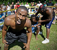 """Charles Woodard, left, revels in defeating Alfonso """"Chocolate"""" Frierson on September 18, 2010. At right is Dhafir Harris, """"Dada 5000"""". .Dada 5000 puts on backyard fights at his mother house, which go viral on youtube and have been the subject of documentaries. Sometimes the men fight until they are unconscious. There' s no gloves and occasionally, there's a cage. The community has taken to the events, because they are able to set up businesses selling food and washing cars."""