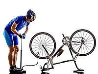 cyclist repairing bicycle in silhouette on white background
