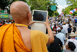 © Licensed to London News Pictures. 16/05/2014. A buddhist monk takes a photo of the protest with his tablet during a rally outside Parliament in Bangkok Thailand where key senators were holding a meeting on May 16, 2014.  Photo credit : Asanka Brendon Ratnayake/LNP