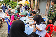 07 JULY 2013 - NARATHIWAT, NARATHIWAT, THAILAND:  Thai Muslim civilians wait to receive free health screenings from Royal Thai Marine medics in Narathiwat. Royal Thai Marines in Narathiwat province held a special ceremony Sunday in advance of Ramadan. They presented widows, orphans and indigent people with extra rice and food as a part of the Thai government's outreach to resolve the Muslim insurgency that has wracked southern Thailand since 2004. The Holy Month of Ramadan starts on about July 9 this year. Muslims are expected to fast from dawn to dusk, engage in extra prayers, recitation of the Quran and perform extra acts of charity during Ramadan. It is the holiest month of the year for Muslims.   PHOTO BY JACK KURTZ
