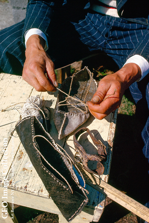 A man sews a pair of leather moccasins.