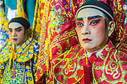 27 APRIL 2013 - BANGKOK, THAILAND:   Chinese opera performers wait to go on stage at a Chinese opera in the Talat Noi neighborhood of Bangkok's Chinatown. Chinese opera was once very popular in Thailand and is usually performed in the Teochew language. Millions of Chinese emigrated to Thailand (then Siam) in the 18th and 19th centuries and brought their cultural practices with them. Recently its popularity has faded as people turn to performances of opera on DVD or movies. There are as many 30 Chinese opera troupes left in Bangkok. They travel from Chinese temple to Chinese temple performing on stages they put up in streets near the temple, sometimes sleeping on hammocks they sling under their stage. The opera troupes are paid by the temple, usually $700 to $1000 a night. PHOTO BY JACK KURTZ