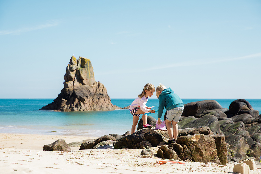 Girl and boy playing on the rocks and building sand castles at Beauport Beach, with the calm blue sea in the background on this sunny summer day in Jersey, CI