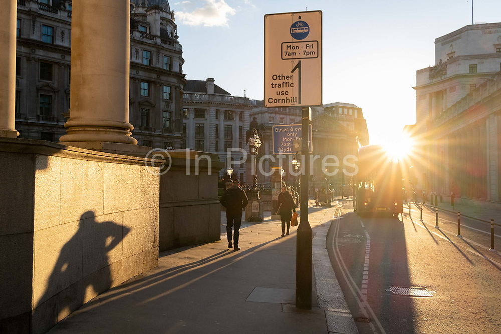 With most Londoners still working from home, a commuter leaves their shadow on a wall of Royal Exchange while walking along a quiet Threadneedle Street during the evening rush-hour during the third lockdown of the Coronavirus in the City of London, the capitals financial district, on 26th February 2021, in London, England.