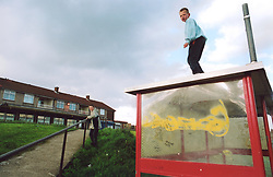 Boys playing on bus shelter on run down council estate; Bradford UK