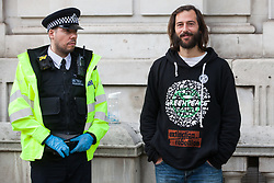 London, UK. 9 October, 2019. Police officers arrest George Barda, a climate activist from Extinction Rebellion, who had locked himself to a fellow activist with an arm tube in order to assist with the blocking of Whitehall on the third day of International Rebellion protests.