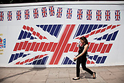 Woman walks past a Union Jack flag hoarding covering a site in central London, UK. The sight of flags around the city has become more and more prominent as nationalism / patriotism takes hold around the time of the 2012 Olmpic Games.