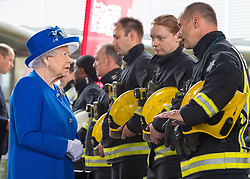 Queen Elizabeth II meets firefighters during a visit to the Westway Sports Centre, London, which is providing temporary shelter for those who have been made homeless by the fire at Grenfell Tower.