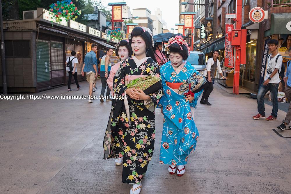 Three Geisha walking on Dempoin Street to engagement in Asakusa district of Tokyo Japan