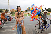 Chanthy in her mother's arms near the riverbank and pagodas, there are balloons sold there..Chanthy, a young girl, learns the Apsara traditional Khmer dance style, at the School of Beaux Arts outside Phnom Penh. This dance style is particularly inspired by thousands of Apsara statues found at Angkor Wat and performed by the Cambodia Royal Ballet. Chanthy lives with her family in Phnom Penh, her father is a policeman, and her family lives in a municipal apartment block surrounded by other families. Chanthy has good friends including a Chinese girl who is mentally handicapped and lives next door. She loves to visit Phnom Penh city and sites with her mother and father, on his scooter.