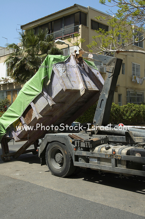 Truck loading a full covered container of building material waste