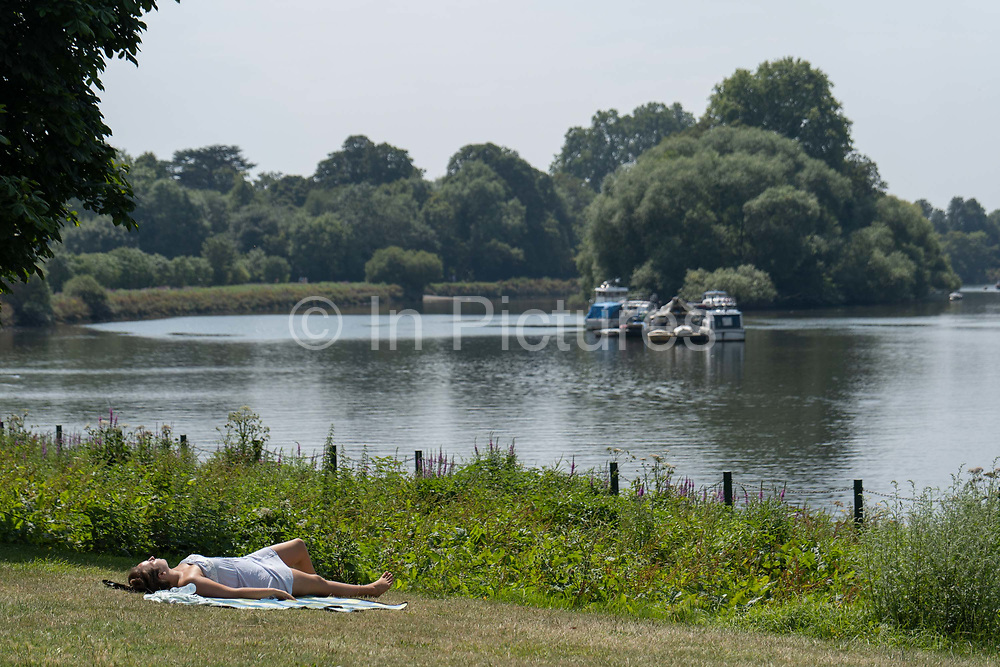 A woman sunbathing along Richmond riverside as record temperatures soar across England on the 25th July 2019 in Richmond in the United Kingdom. The Met Office has estimated that parts of England could reach a record-breaking 39C this afternoon.