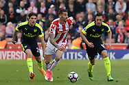 Geoff Cameron of Stoke city goes past Mersut Ozil of Arsenal ® and Hector Bellerin of Arsenal. Premier league match, Stoke City v Arsenal at the Bet365 Stadium in Stoke on Trent, Staffs on Saturday 13th May 2017.<br /> pic by Bradley Collyer, Andrew Orchard sports photography.