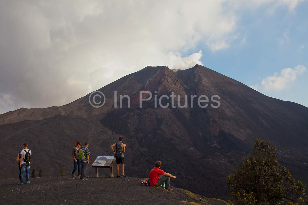 A young male traveller looking at Pacaya - an active volcano in Guatemala, near the old Colonial capital city of Antigua in the Escuintla Department. It is a popular one day trek for tourists and travellers, accessed from Antigua. Although the volcano is active, it is on the most part safe to climb.