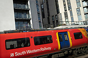 Seen from a passing train carriage window, a South Western Railway train carriage travels along parallel rails with new apartment properties above, on 12th November 2020, in London, England.