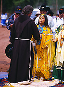 Catholic Priest, Father blessing Carla Goseyun with corn pollen, Carla Goseyun's White Mountain Apache Traditional Sunrise Ceremony, Whiteriver, Arizona.  Please Note: A small extra licensing fee needs to be paid to the Goseyun Family for usage of this photo. Contact Fred Hirschmann for more information. Thanks.