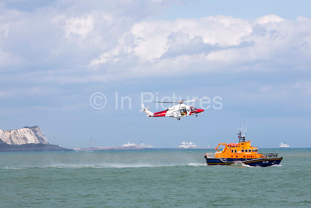 The HM Coastguard rescue helicopter G-C1JW  flying in front of the White Cliffs as it attempts to land a crew member on the back of the Royal National Lifeboat Institution RNLI Dover Life boat 17-09 during a training exercise in the sea just outside Folkestone Harbour, Folkestone, Kent. UK.