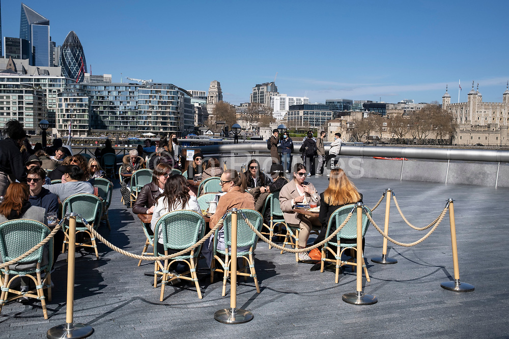 People enjoying some al fresco dining at tables outside a restaurant at More London and overlooking the cityscape and skyline of the City of London financial district on 17th April 2021 in London, United Kingdom.