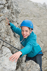 Smiling young teenager climbing helmet rope