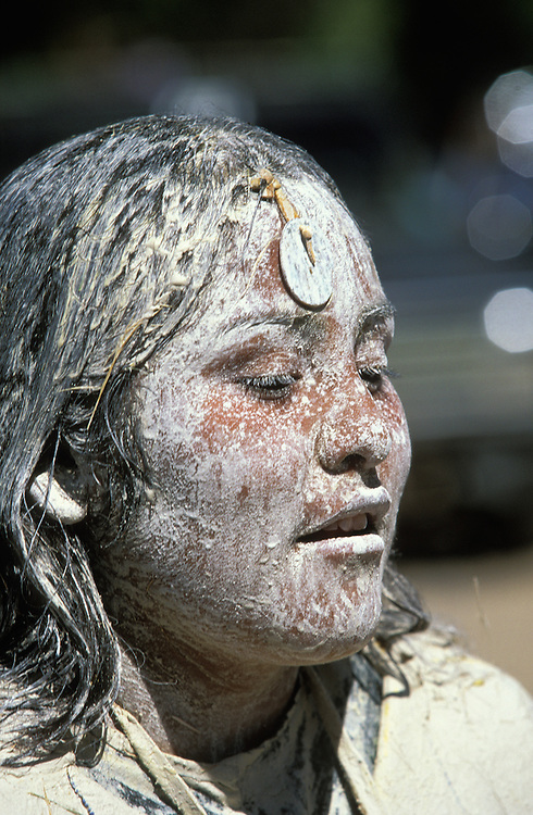An Apache girl covered in sacred white clay and corn meal at her Sunrise Dance, a first menstruation rite, on the San Carlos Apache Indian Reservation in Arizona, USA. The painting of the girl with the white clay is both a blessing and an enactment of certain parts of the Apache creation myth. During the rites the girl becomes Changing Woman, a mythical female figure, and comes into possession of her healing powers. The rites are also supposed to prepare the girl for adulthood and to give her a long and healthy life without material wants.