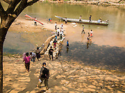 "01 MARCH 2014 - MAE SOT, TAK, THAILAND: Burmese walk down to the Moie River in Mae Sot, Thailand, to board a small boat (in the background) to take them back to Myawaddy, Myanmar. Mae Sot, on the Thai-Myanmar (Burma) border, has a very large population of Burmese migrants. Some are refugees who left Myanmar to escape civil unrest and political persecution, others are ""economic refugees"" who came to Thailand looking for work and better opportunities.    PHOTO BY JACK KURTZ"