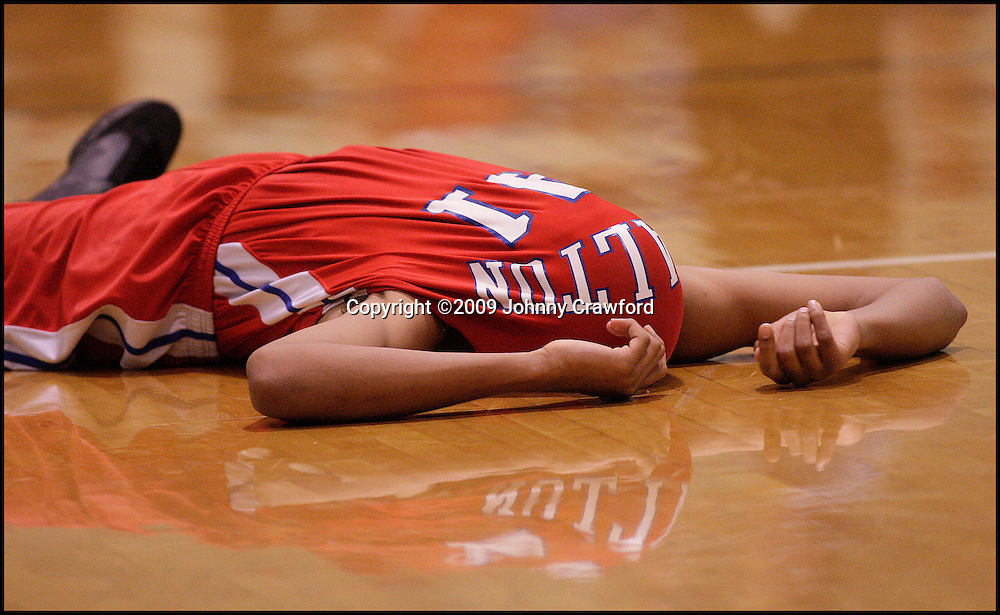 When I saw Walton High School's Glen Rice (41) remains on  the floor with his shirt pulled over his face  after his team lost 61 to 64 to Norcross High School  on Wednesday, March 4, 2009. I knew I had a great picture. Because the picture was shot clean and tight and he was wearing a red jersey, I knew the picture would look good in the paper big or small.JOHNNY CRAWFORD