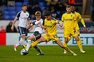 Ronan Darcy of Bolton Wanderers and Callum Reilly of Wimbledon contest a loose ball during the EFL Sky Bet League 1 match between Bolton Wanderers and AFC Wimbledon at the University of  Bolton Stadium, Bolton, England on 7 December 2019.