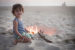 Boy sitting next to camp fire on beach and family in the background, Lit-et-Mixe, Aquitaine, France