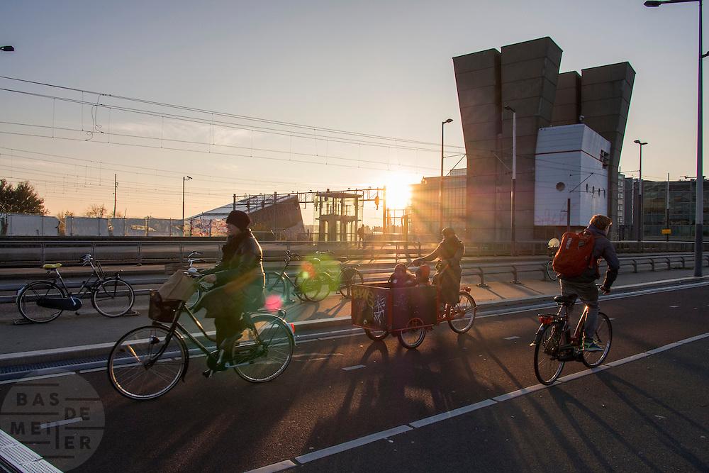 In Amsterdam fietsen mensen, waaronder een vrouw met kinderen in de bakfiets, over een brug bij de Prins Hendrikkade.<br /> <br /> In Amsterdam cyclist, amongst others a woman with her children on a cargo bike, ride over a bridge near the Prins Hendrikkade.