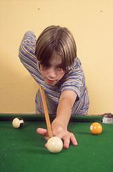 Teenage boy playing pool,
