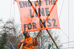 Dan Hooper, widely known as Swampy during the 1990s, looks at a banner from a basket suspended from a bamboo tripod positioned in the river Colne on 8th December 2020 in Denham, United Kingdom. The climate and roads activist had occupied the tripod the previous day in order to delay the building of a bridge as part of works for the controversial HS2 high-speed rail link and a large security operation involving officers from at least three police forces, National Eviction Team enforcement agents and HS2 security guards was put in place to facilitate his removal.