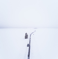 Aerial view of a car driving on a snowy road in the blizzard on Vormsi island, Estonia.